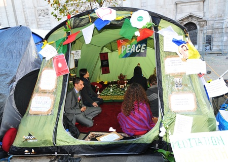 occupying: London, UK - 19 Nov, 2011: Occupy London protesters meditate and pray for world peace in a tent at Saint Paul Cathedral in London  Editorial