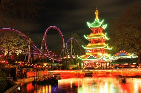 Copenhagen, Denmark - 19 Dec, 2011: Night view of colorful Chinese pagoda reflected in water at Tivoli Gardens