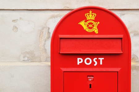 Copenhagen, Denmark - 19 Dec, 2011: Red postal box against grunge wall in Copenhagen, Denmark
