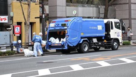 Tokio, Japonia - 28 grudnia 2011: Śmieciarka i pracownicy Zdrowotność na ulicach Tokio
