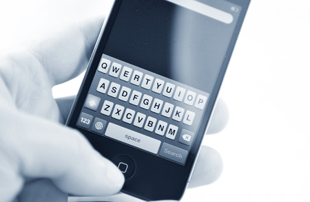 London, UK - 27 Feb, 2012: Hand holding iPhone with blank message against white background