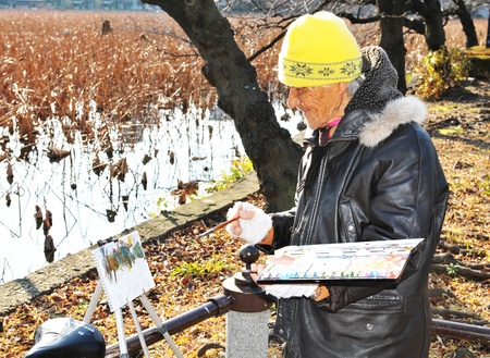 art therapy: Tokyo, Japan - 28 December, 2011: Octogenarian Japanese man painting outdoors in Ueno Park in winter Editorial