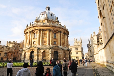 Oxford, UK - November 12, 2011: Tourists visiting the Radcliffe Camera, a famous building in Oxford, designed in the English Palladian style