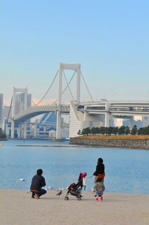 Tokyo, Japan - 2 January, 2012: Japanese family enjoying the view of the Rainbow Bridge in Daiba, Tokyo Stock Photo - 13022350