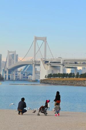 Tokyo, Japan - 2 January, 2012: Japanese family enjoying the view of the Rainbow Bridge in Daiba, Tokyo Stock Photo - 13022350
