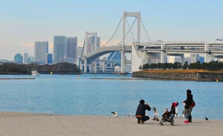 Tokyo, Japan - 2 January, 2012: Japanese family enjoying the view of the Rainbow Bridge in Daiba, Tokyo
