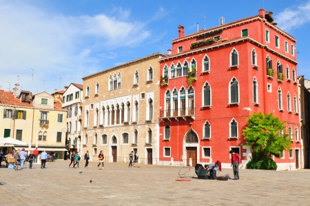 piazza: Venice, Italy - 06 May, 2012: Tourists admiring colorful architecture in Venetian piazza