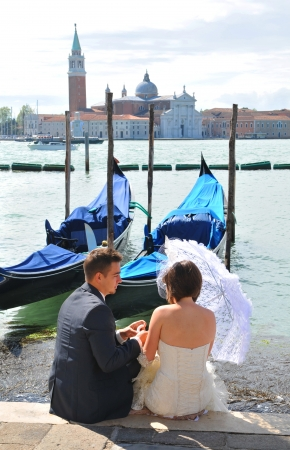 Venice, Italy - 6 May, 2012: Newly married couple on honeymoon enjoy the view of the Venetian Grand Canal Editorial