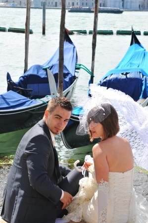 honeymoons: Venice, Italy - 6 May, 2012: Newly married couple on honeymoon enjoy the view of the Venetian Grand Canal Editorial