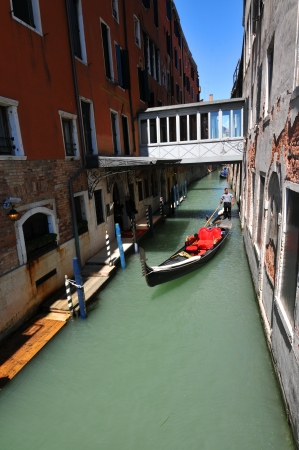 Venice, Italy - 07 May, 2012: Gondola navigates along canal in Cannaregio, major Venetian district