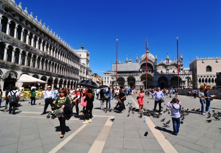 Venice, Italy - 7 May, 2012: Tourists feeding pigeons in the famous San Marco Piazza (St. Mark