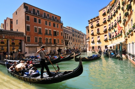 Venice, Italy - 7 May, 2012: Tourists sightseeing in gondola across Venetian canal Stock Photo - 14145142