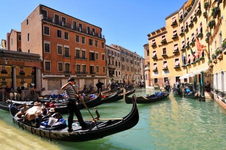 Venice, Italy - 7 May, 2012: Tourists sightseeing in gondola across Venetian canal Stock Photo - 14145142