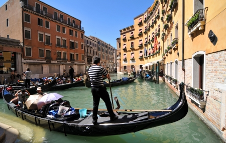 Venice, Italy - 7 May, 2012: Tourists sightseeing in gondola across Venetian canal Stock Photo - 14145137