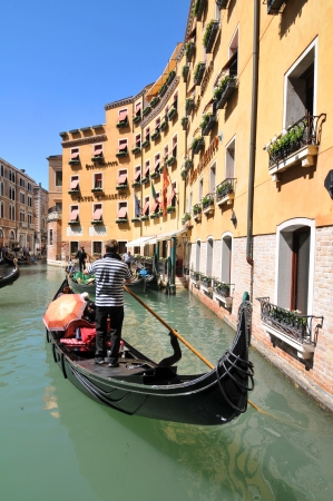 Venice, Italy - 7 May, 2012: Tourists sightseeing in gondola across Venetian canal Stock Photo - 14145135