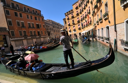 Venice, Italy - 7 May, 2012: Tourists sightseeing in gondola across Venetian canal Stock Photo - 14145131