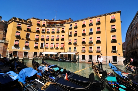 Venice, Italy - 7 May, 2012: Tourists sightseeing in gondola across Venetian canal Stock Photo - 14145138