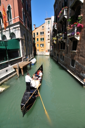 Venice, Italy - 7 May, 2012: Tourists sightseeing in gondola across Venetian canal Stock Photo - 14145125