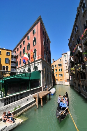 Venice, Italy - 7 May, 2012: Tourists sightseeing in gondola across Venetian canal Stock Photo - 14145124