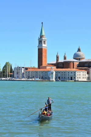 Venice, Italy - 7 May, 2012: Gondola navigating across Venetian canal with San Giorgio Maggiore basilica in the background Stock Photo - 14145084