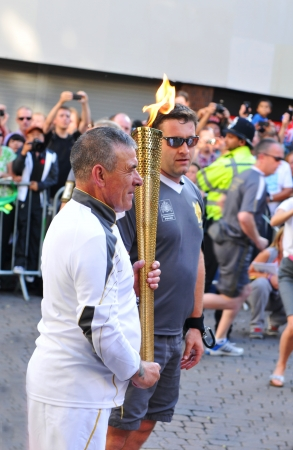 olympiad: Nottingham, UK - 28 June, 2012: Torch bearer lights the Olympic flame during the London 2012 Olympic Torch Relay through Nottingham city