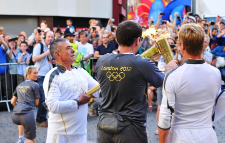 Nottingham, UK - 28 June, 2012: Organizers assist the torch bearers during the London 2012 Olympic Torch Relay through Nottingham city