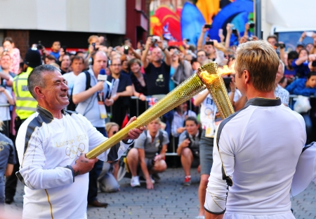 Nottingham, UK - 28 June, 2012: Torch bearer lights the Olympic flame during the London 2012 Olympic Torch Relay through Nottingham city