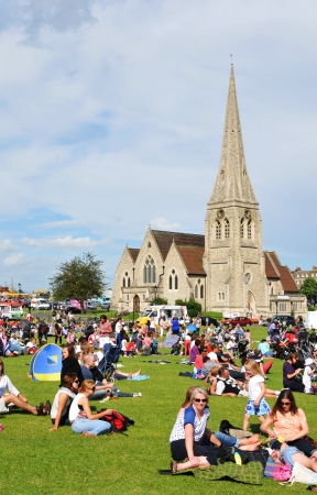 church group: London, UK - August 03, 2012: Old church overlooking groups of people enjoying the sun in Blackheath, a suburb of London, located  in the London Borough of Lewisham.