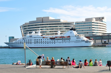 anchoring: Barcelona, Spain - 6 July, 2012: Tourists watching a luxurious cruise ship anchoring in Port Vell marina in Barcelona Editorial