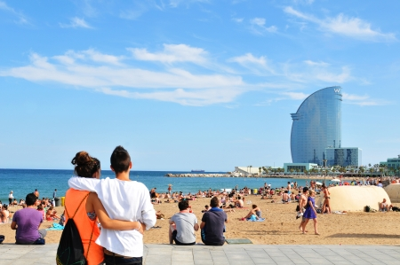 Barcelona, Spain - 6 July, 2012: Young couple of tourists overlooking the Sant Sebasti� beach in Barcelona, Catalonia