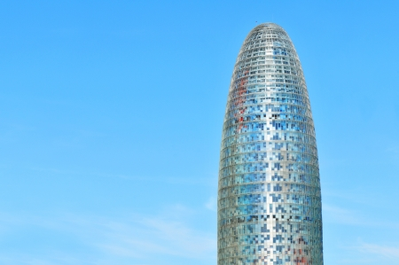 torre: Barcelona, Spain - 08 July, 2012: Architectural detail of the Agbar Tower (Torre Agbar) located in the Poblenou neighborhood of Barcelona, against blue sky