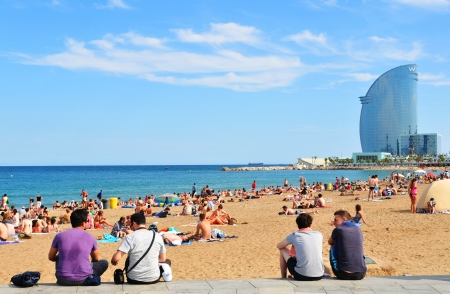 Barcelona, Spain - 6 July, 2012: Tourists sunbathing on Barceloneta beach on a hot summer day