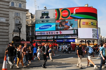 piccadilly: London, UK - 9 August, 2012  Tourists walk in Piccadilly Circus, major commercial area of London, home of important landmarks and shops