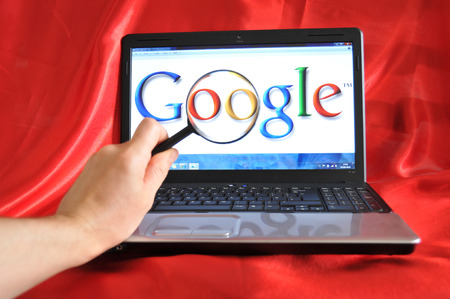 LONDON, UK - SEPTEMBER 3, 2010: Google search concept with hand holding magnifying glass against Google home screen (illustrative editorial)