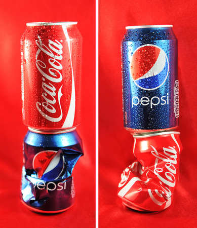 LONDON, UK - FEBRUARY 27, 2011: Coca Cola vs. Pepsi competition concept with cans against red background (illustrative editorial)