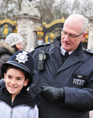ロンドンのローカル首都警官制服が観光客に彼の帽子を与えるロンドン、イギリス - 2011 年 3 月 5 日。