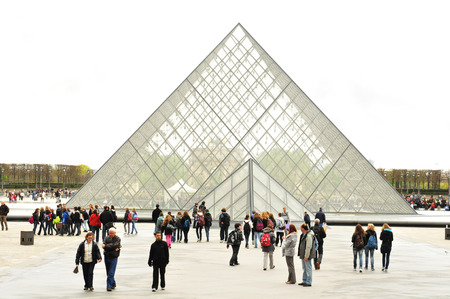 museum visit: PARIS, FRANCE - MARCH 29, 2011: Tourists visit glass pyramid in the main courtyard of the famous Louvre Museum