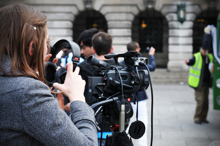 NOTTINGHAM, UK - APRIL 28, 2011: Young female reporter prepares audio-video equipment for street interview