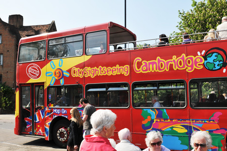 embark: CAMBRIDGE, UK - APRIL 25, 2011: Tourists queue to embark on city sightseeing red bus in central Cambridge Editorial