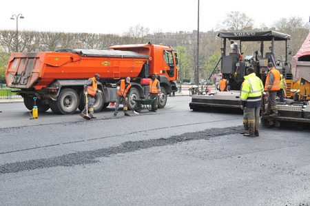 compacting: PARIS, FRANCE - MARCH 29, 2011: Construction workers use heavy equipment to repair roads in central Paris