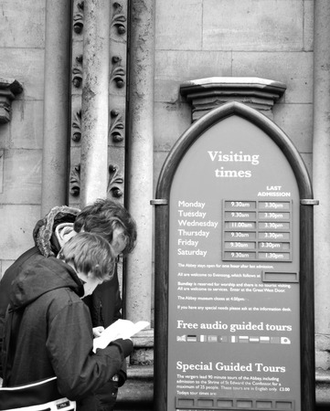 guided: LONDON, UK - NOVEMBER 19, 2011: Tourists check visiting hours at Westminster Abbey, major tourist landmark in London