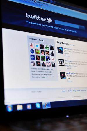 LONDON, UK - JANUARY 27, 2011: Close up of Twitter home page with mobile application on laptop screen.