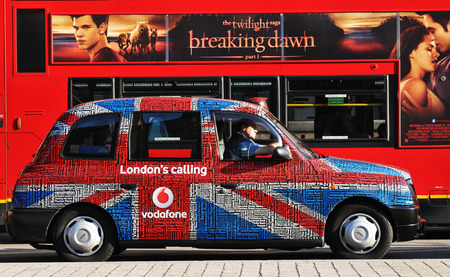 union jack: LONDON, UK - NOVEMBER 18, 2011: Old taxi tuned with Union Jack flag against traditional double-decked red bus on London streets