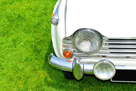30 s: Vintage car detail against green grass background