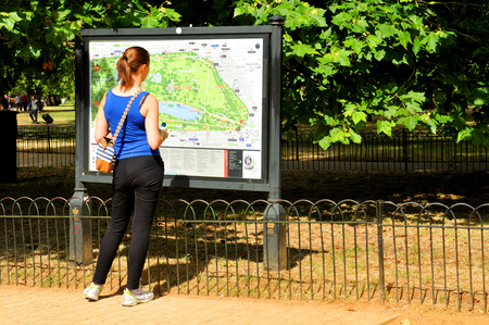 hyde: LONDON, UK - JULY 9, 2014: Tourist looks for directions on map at the entrance to the Hyde Park in London Editorial