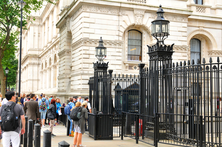 british english: LONDON, UK - JULY 9, 2014: Tourists gather outside 10 Downing Street in London, the official residences of the Prime Minister