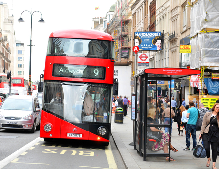 LONDON, UK. JULY 9, 2014: Modern red double decker bus stops at bus stop in central London