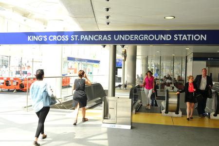 rail cross: LONDON, UK. JULY 9, 2014: People enter the Kings Cross underground station in London.