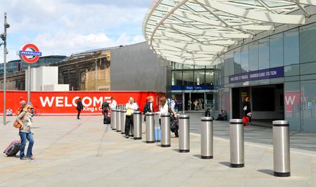 rail cross: LONDON, UK. JULY 9, 2014: People enter the Kings Cross train station in London.
