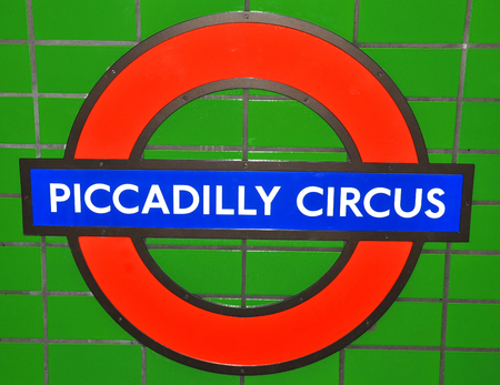 piccadilly: LONDON, UK. JULY 9, 2014: Abstract detail of London Piccadilly Circus underground sign against colourful tiles.